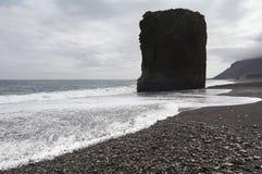 Den massiva monoliten vaggar på en isländsk strand Arkivfoto