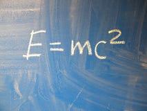 Den matematiska formeln e=mc2 kvadrerade skriftligt på en blått, förhållandevis smutsig svart tavla vid krita arkivfoton