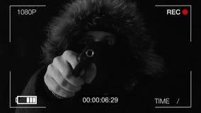 Den med huva mannen i en maskering hotar med vapnet, svart bakgrund lager videofilmer