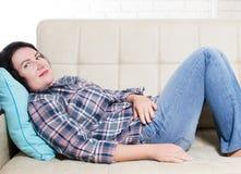 Den medelåldersa fridfulla stillsamma kvinnan som ler att ligga på hemmastadd rumflicka för soffa, har avbrottet efter arbete, el fotografering för bildbyråer