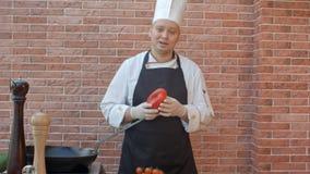 Den medelåldersa kocken i det vita enhetliga stående near skrivbordet som talar till kameran med grönsaken i hans händer, ordnar  Royaltyfri Bild
