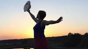 Den medelåldersa kvinnan dansar på en sjöbank på solnedgången lager videofilmer