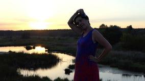 Den medelåldersa kvinnan kammar hennes hår på solnedgången stock video