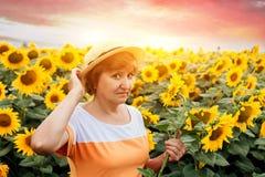 Den medelåldersa kvinnan samlar solrosor i fältet arkivbilder