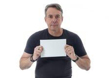 Den medelåldersa mannen bär den svarta t-skjortan Han rymmer en vitbok Arkivfoto