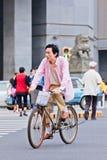 Den medelåldersa mannen cyklar i centrum av Kunming, Kina Arkivbilder
