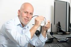 Den medelåldersa mannen gör ren hans exponeringsglas i hans kontor royaltyfri bild