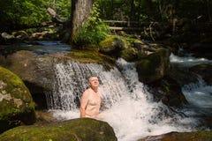 Den medelåldersa mannen tar ett wellnessbad i en flod Arkivbild