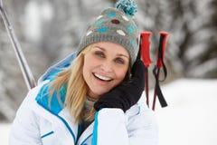 Den medelåldriga kvinnan skidar på ferie i berg Arkivfoton