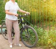 Den medel?ldersa attraktiva slanka kvinnan i ljus byxa och skjortast?llningar n?ra cykeln i parkerar p? en solig sommardag som cy royaltyfria foton