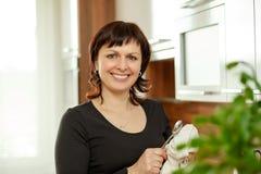 Den medelåldersa kvinnan torkar disken i köket Arkivfoton