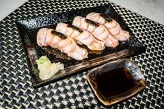 Den medelsällsynta nötköttsushi på en svart platta är klar att tjäna som i japansk stil royaltyfri bild