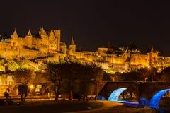 Den medeltida fästningen i upplyst i ovannämnd bakgrund parkerar vid floden Royaltyfri Fotografi