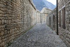 Den medeltida gatan med väggen som göras av, vaggar och kiselstenar i villan Fotografering för Bildbyråer