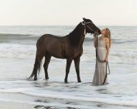Den medeltida kvinnan och hästen bevattnar in Arkivbilder