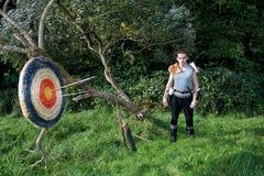 Den medeltida mannen står i naturen Pilen, kurvan och darrning står förutom och målet från sugrör med pilar Royaltyfri Foto