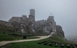 Den medeltida slotten fördärvar att sitta överst av kullen i tung dimma Arkivbild
