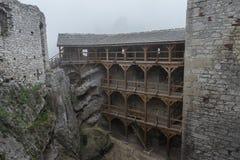 Den medeltida slotten fördärvar borggården i tung dimma Arkivfoto