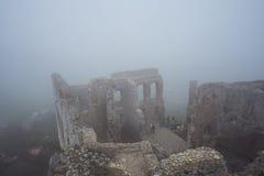 Den medeltida slotten fördärvar i sikt för tung dimma från hög poäng Royaltyfri Foto