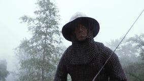 Den medeltida soldaten i metallharnesk slåss med hans svärd lager videofilmer