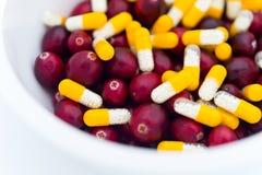 Medicinsk blandning av guling-vit pills och nya cranberries i bunken Arkivfoton