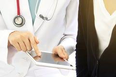 Den medicinska doktorn diskuterar med patienten om de vård- undersökningsresultaten royaltyfria bilder