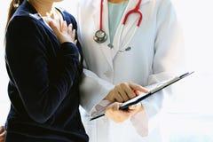 Den medicinska doktorn diskuterar med patienten om de vård- undersökningsresultaten, bekymrad patient med hennes doktor i medicin royaltyfria foton