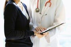 Den medicinska doktorn diskuterar med patienten om de vård- undersökningsresultaten, bekymrad patient med hennes doktor i medicin royaltyfria bilder