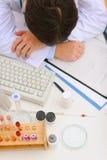 Den medicinska doktorn som sovar på skrivbordet med läkarundersökning, stoppar royaltyfri foto