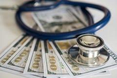 Den medicinska hörlurar förlade dollarpengar, på skrivbordet arkivbilder