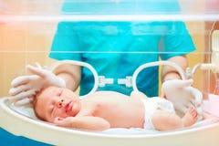 Den medicinska personalen som tar omsorg av nyfött, behandla som ett barn i begynnande kuvös royaltyfria bilder