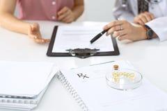 Den medicinska receptformen, kapslar och preventivpillerar ligger mot bakgrunden av en doktor och en patient som diskuterar hälsa Arkivbild