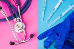 Den medicinska skyddshandskesidan - förbi - sid med injektionssprutor med läkarbehandlingar och den medicinska stetoskopet färgar Royaltyfria Bilder