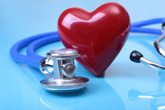 Den medicinska stetoskopet och röd hjärta på blått avspeglar bakgrund arkivfoton