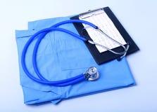 Den medicinska stetoskopet som ligger på tålmodig lista för medicinsk historia, RX-receptet och blått manipulerar den enhetliga c royaltyfri bild