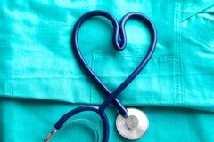 Den medicinska stetoskopet som vrids i hjärtaform som ligger på tålmodig lista för medicinsk historia, och blått manipulerar den  arkivfoto