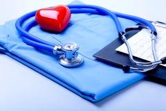 Den medicinska stetoskopet, den tålmodiga listan för medicinsk historia, RX-receptet, röd hjärta och blått manipulerar den enhetl arkivbild