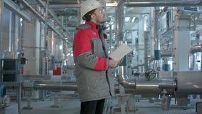 Den mekaniska inspektören gör kontroll på en växt lager videofilmer