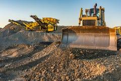 Den mekaniska transportbandet och grävskopan som ska pulvriseras, vaggar och stenar och frambringar grus royaltyfria foton