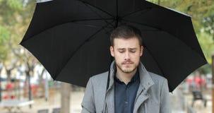 Den melankoliska mannen som går i, parkerar en regnig dag stock video