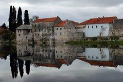Den melankoliska platsen med hus reflekterade på floden i Bosnien och Hercegovina Royaltyfri Bild