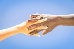 Den mellan skilda raser människan räcker korsningen fingrar för kamratskap och förälskelse Royaltyfri Foto