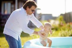 Den mellersta ålderfadern och hans behandla som ett barn sonen som har gyckel av simbassängen Arkivbild