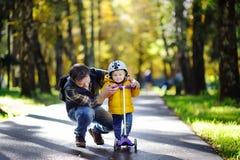 Den mellersta ålderfadern som visar hans litet barnson hur man rider en sparkcykel i en höst, parkerar arkivbild