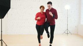 Den mellersta ålderkvinnan och den unga mannen dansar kizomba i studio arkivfilmer