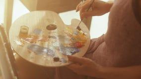 Den mellersta åldriga kvinnakonstnären målar på kanfassammanträde i dagsljuskonststudio lager videofilmer