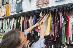 Den mellersta åldriga kvinnan köper kläder på det begagnade lagret Arkivfoton