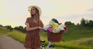 Den mellersta planflickan i klänning går med cykeln och blommor i fältet arkivfilmer