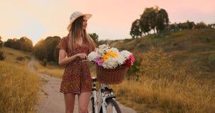 Den mellersta planflickan i klänning går med cykeln och blommor i fältet lager videofilmer