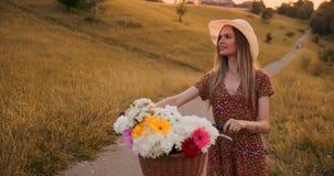 Den mellersta planflickan i klänning går med cykeln och blommor i fältet stock video